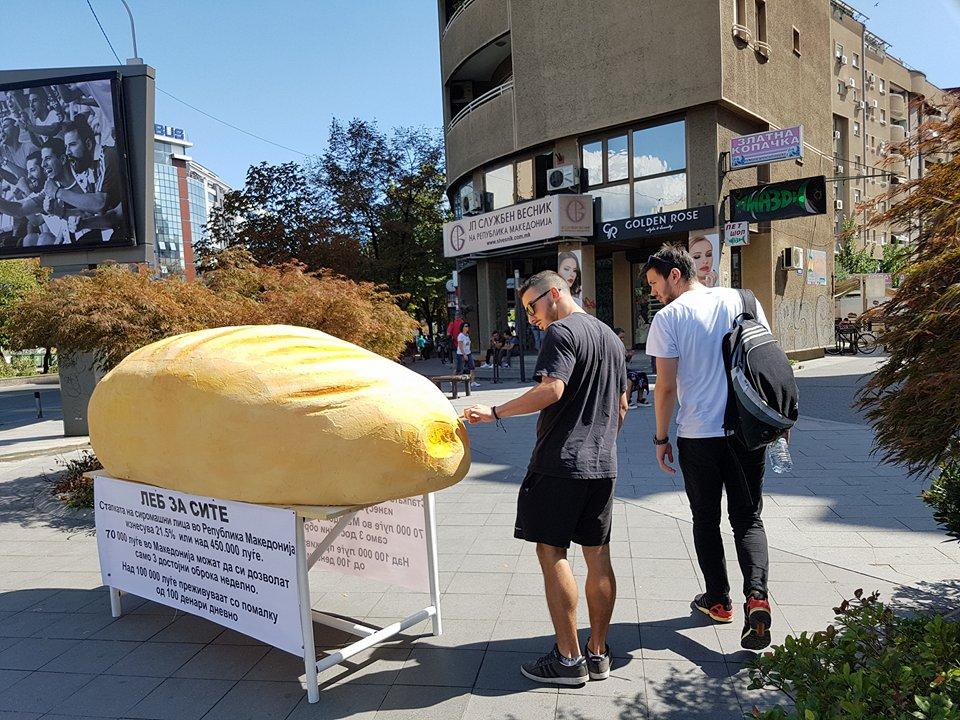 Џиновска векна леб ги потсетува минувачите дека нивните сограѓани живеат во глад